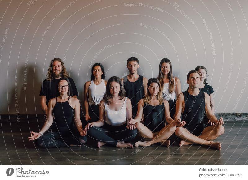 Gruppe von ruhigen, entspannten Athleten, die zusammen Yoga praktizieren und in einem hellen, modernen Trainingsraum eine Lotus-Pose ausführen meditieren