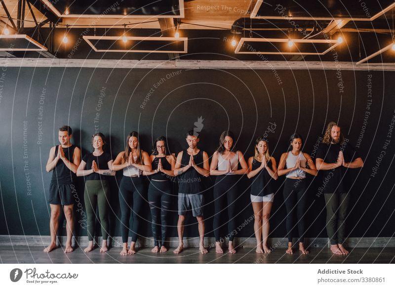 Fröhliche Athleten praktizieren gemeinsam Yoga in Berghaltung im modernen Trainingsraum sich[Akk] entspannen Berg-Pose meditieren Klasse Namaste Übung tadasana