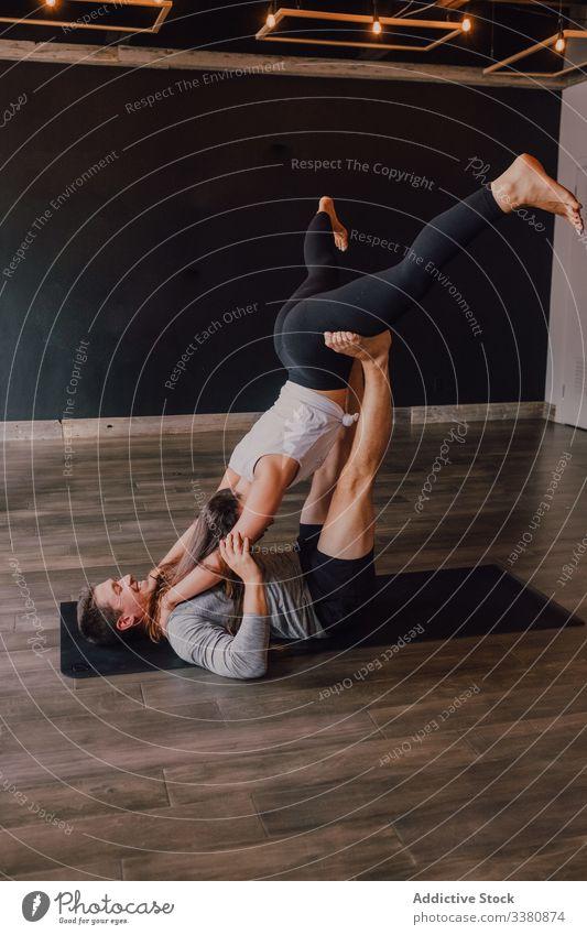 Fröhliches Paar trainiert gemeinsam stehend in gefalteter Blattstellung auf der Matte im Studio Akro-Yoga gefaltete Blattstellung Gleichgewicht Partner heiter