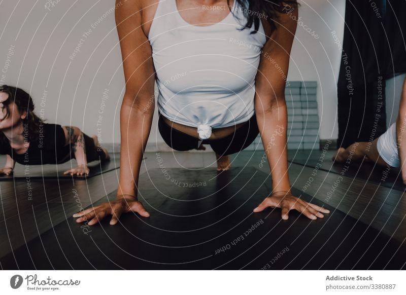Frau praktiziert Yoga in fliegender Taubenstellung üben fliegende Taube Pose Körper Barfuß Training einbeiniges Brett Klasse Fitness Atelier positionieren
