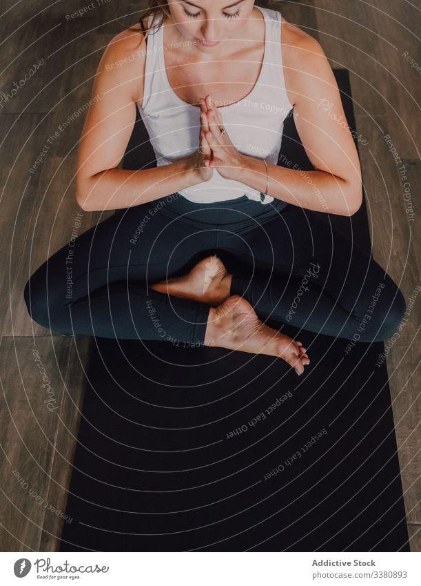 Schlanke barfüßige Frau meditiert in gebundener Winkelhaltung im zeitgenössischen Trainingsraum Meditation Yoga sich[Akk] entspannen Randwinkelstellung üben