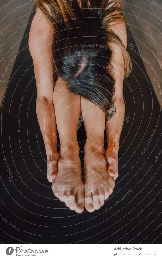 Fleißige Frau praktiziert Yoga in sitzender Vorbeugeposition, während sie Unterricht im zeitgenössischen Studio hat sitzende Vorwärtsbeuge üben Pose beweglich
