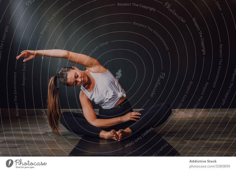 Schlanke barfüßige Frau, die ihren Körper in gebundener Winkelhaltung im zeitgenössischen Studio dehnt Yoga üben Randwinkelstellung Dehnung Übung Training