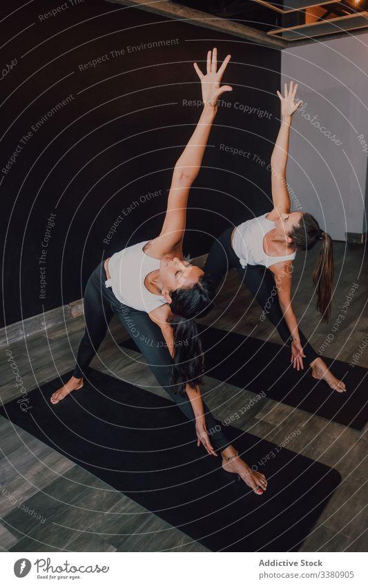 Frauen, die ihren Körper dehnen und Yoga in gedrehter Dreieckshaltung praktizieren drehbare Dreieckshaltung Übung üben Gleichgewicht Dehnung Unterlage Klasse