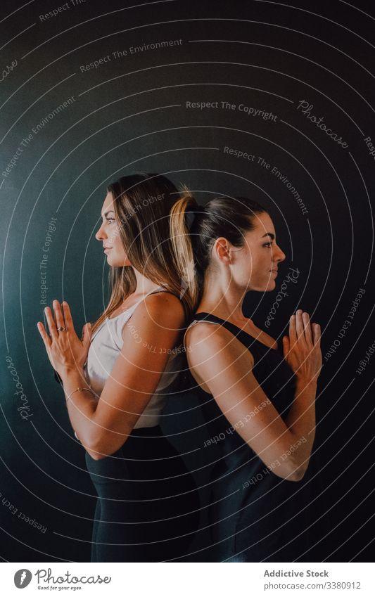 Passende erwachsene Frauen in Berghaltung mit Namaste in dunkler Kammer sich[Akk] entspannen Yoga Windstille meditieren Figur Berg-Pose Training Athlet passen