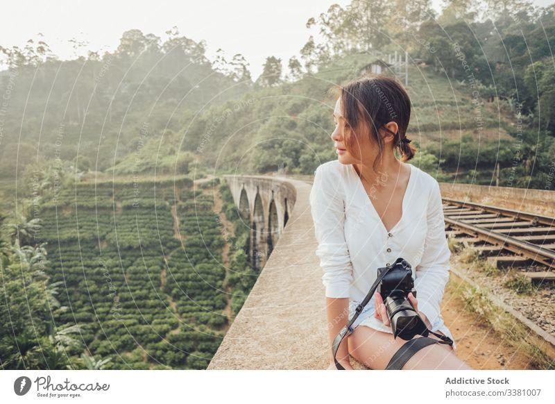 Junge Asiatin im Urlaub beim Fotografieren mit der Kamera in der Natur Frau Märchenfoto Fotokamera reisen exotisch Dschungel Eisenbahn erkunden Ansicht