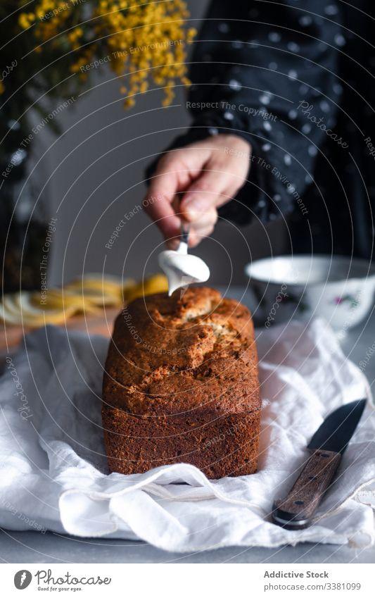 Frau setzt Schlagsahne auf Kuchen selbstgemacht Sahne gepeitscht dekorieren Hand Lebensmittel backen Gebäck Zitrone geschmackvoll Tisch Küche lecker vorbereiten