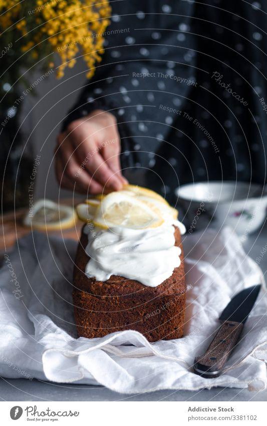 Hausfrau dekoriert Kuchen mit Zitronenscheiben selbstgemacht dekorieren Scheibe Hand Frau Lebensmittel backen Gebäck Zitrusfrüchte Zuckerguß geschmackvoll Küche
