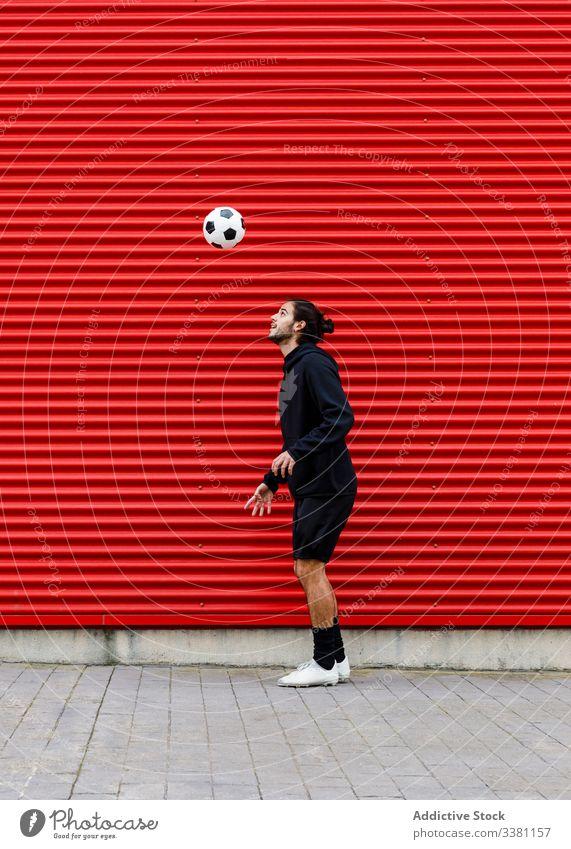 Mann spielt Fussball auf der Strasse Fußball Ball Kopf Training Finte Kick spielen Sport Aktivität Spiel männlich Energie Straße urban Bewegung Gesundheit