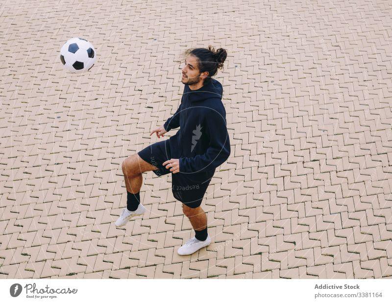 Sportler, der einen Fussball mit dem Knie kickt Mann Fußball Ball Kick Straße Straßenbelag Training Aktivität männlich Spiel Sportbekleidung Spieler Athlet