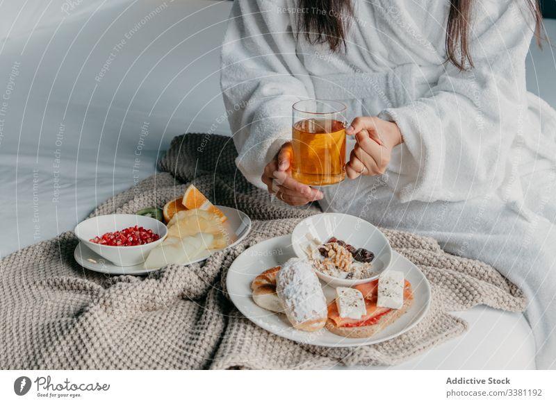 Anonyme Frau beim Frühstück im Bett Tee Glück Bademantel heiter Becher Tasse trinken Lebensmittel gemütlich geschmackvoll heimwärts sich[Akk] entspannen frisch