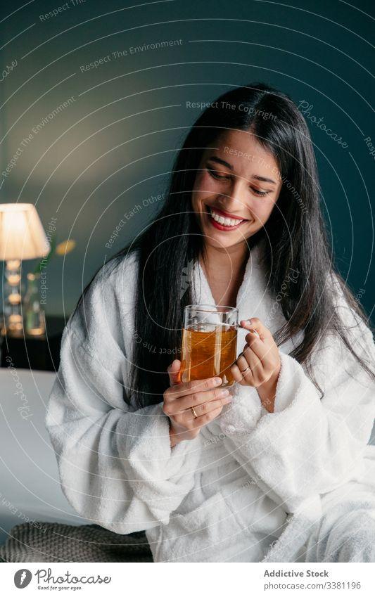 Entspannte Frau im Bademantel genießt Tee sich[Akk] entspannen ruhen trinken Morgen Fenster Becher gemütlich Getränk Tasse Glas Lifestyle jung heimwärts Komfort