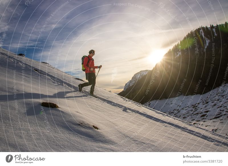 Frau mit Wanderrucksack und Wanderstöcke im Gebirge, schneebedeckte Landschaft im Winter. berge gebirge sonnenuntergang alpen Berchtesgadener Alpen Spuren
