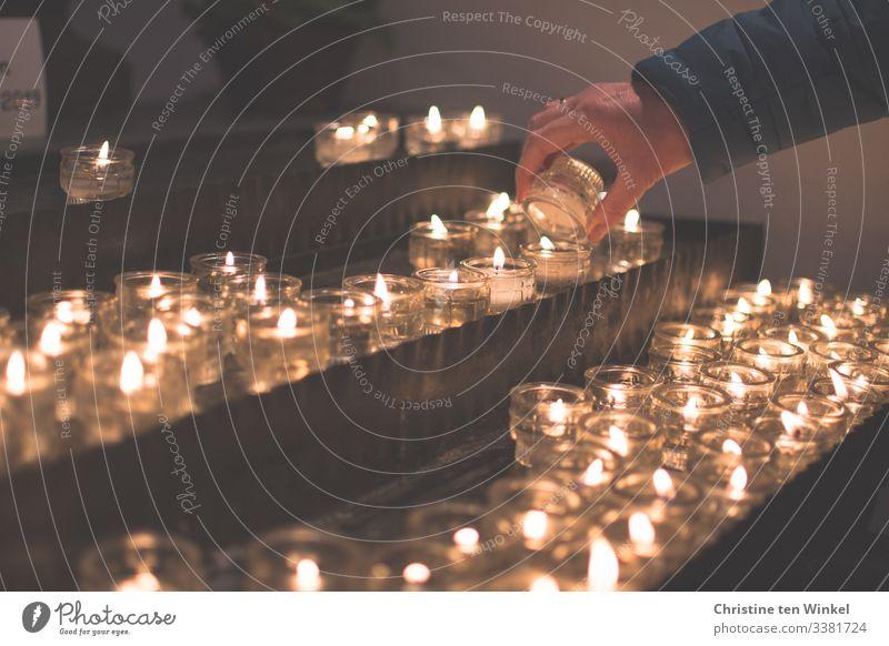 Frau zündet eine Kerze an einem Kerzenaltar an Mensch feminin Erwachsene Hand 1 30-45 Jahre 45-60 Jahre Kerzenschein Kerzenstimmung Kerzenglas Kerzenflamme