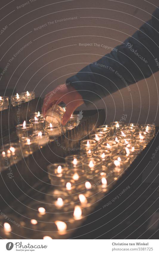 Frau zündet eine Kerze an einem Kerzenaltar an feminin Erwachsene Hand 1 Mensch 30-45 Jahre 45-60 Jahre Kerzenschein Kerzenstimmung Kerzenflamme Kerzenglas