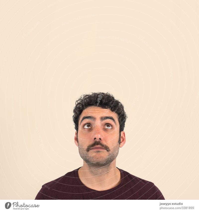 Lustiges Porträt eines kleinen Jungen mit Schnurrbart, der mit zweifelndem und verwirrtem Gesicht nach oben schaut. Violettes T-Shirt und isolierter ockerfarbener Hintergrund.