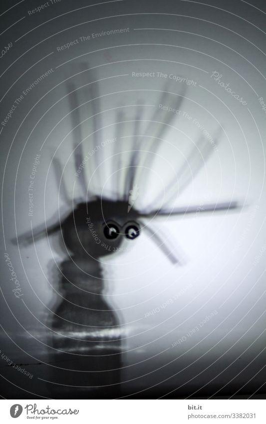 schwarzes Männlein mit abstehenden Haaren und Glubschaugen, schaut traurig nach unten, bestehend aus Licht und Schatten, in einer Traumwelt. Kunst
