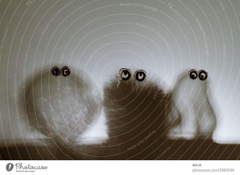 Drei lustige Figuren gebastelt aus Kugel, Bürste und Sieb, mit aufgeklebten Augen, stehen vor einer weissen Wand. Einsamkeit dunkel Zwerg Gnom witzig