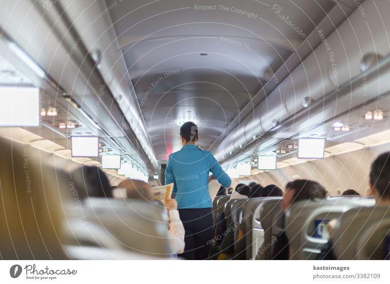 Innenraum eines Verkehrsflugzeuges mit Stewardess, die die Passagiere während des Fluges auf den Sitzen bedient. Flugbegleiterin Flugzeug Fluggerät Innenbereich