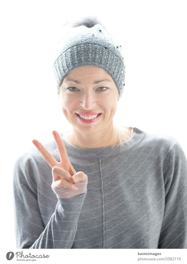 Nahaufnahme eines Porträts einer fröhlichen kaukasischen Frau, die ein Friedenszeichen gestikuliert und lächelt Zeichen Mädchen schön Glück Hut Lächeln weiß