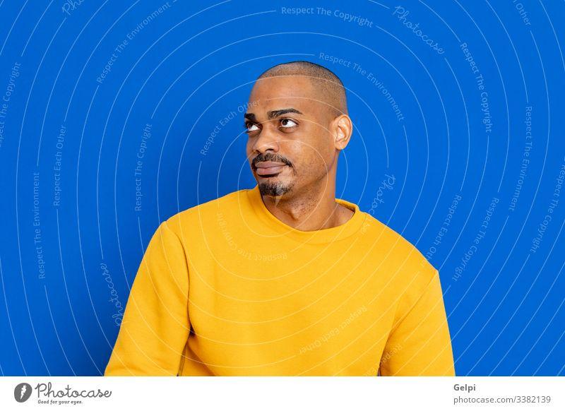 Afrikaner mit gelbem Trikot schwarz Typ blau rot Glück Lächeln freudig positiv entspannt Blick Erwachsener Menschen Person Afrikanisch männlich Amerikaner Mann