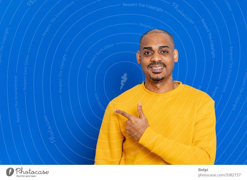 Afrikaner mit gelbem Trikot schwarz Typ blau Punkt zeigen hindeutend Finger Inserat Anzeige Erwachsener Menschen Person Afrikanisch männlich Amerikaner Mann