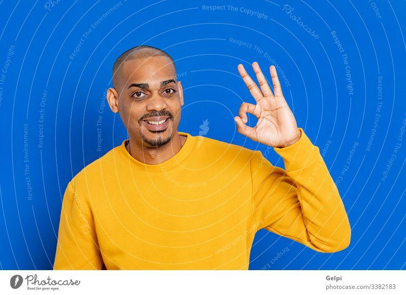 Afrikaner mit gelbem Trikot schwarz Typ blau OK akzeptieren ja Glück Lächeln lustig Seufzer Finger Hand Erwachsener Menschen Person Afrikanisch männlich