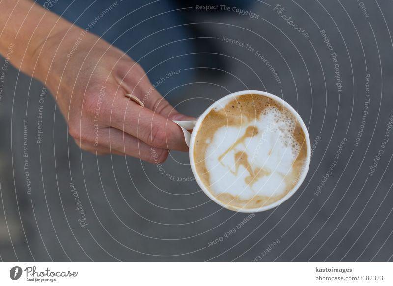 Hand hält eine Tasse Kaffee zum Mitnehmen. gehen Sie Latte Papier Kunst weg Top Ansicht Kunststoff trinken Einwegartikel Cappuccino Café weiß Arbeit schwarz