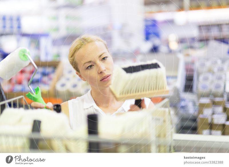Junge unabhängige Frau kauft Werkzeuge für die Hausdekoration in einem Geschäft für Malerbedarf. Werkstatt Laden Farbe Rolle Wahl Mädchen heimwärts Renovierung