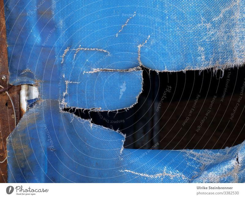 Riss in blauer LKW Plane Abdeckplane zerrissen kaputt Transport Güterverkehr Gütertransport Abdeckung Loch Blache textil Schutz Lastwagen