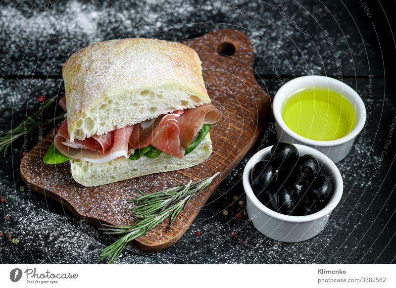Ciabatta-Sandwich mit Rucolasalat, Blattspinat und Speck. Salatbeilage Spinat Belegtes Brot Oliven Rosmarin Erdöl Olivenöl Italien Bruschetta Lebensmittel Mehl