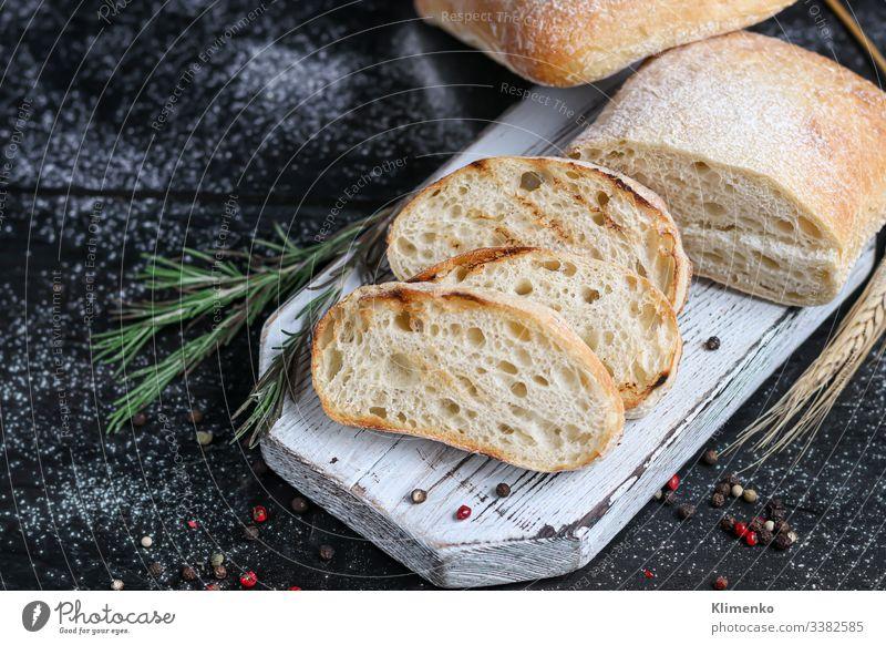 Ciabatta mit Rosmarin, Olivenöl und Kirschtomaten auf einem Holzbrett. Auf einem dunklen Hintergrund. Salatbeilage Spinat Speck Belegtes Brot Erdöl Italien