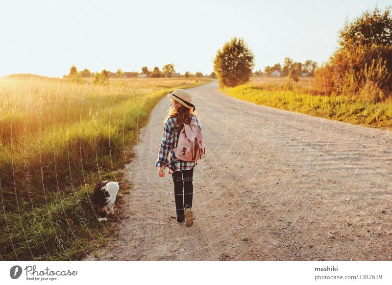 glückliches Kind Mädchen, das mit seinem Hund auf der Landstraße spazieren geht. Sommerferien genießen, ländliches Wohnkonzept Natur im Freien Glück Straße