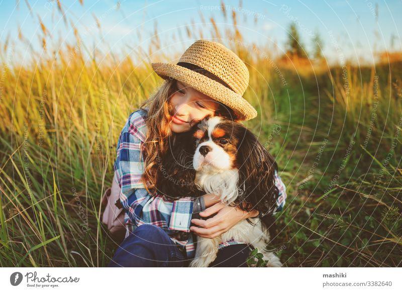 fröhliches Mädchen, das mit seinem Hund die Sommerferien genießt und auf der sonnigen Wiese spazieren geht und spielt. Reisen, Erkundung neuer Orte und ländliches Wohnkonzept