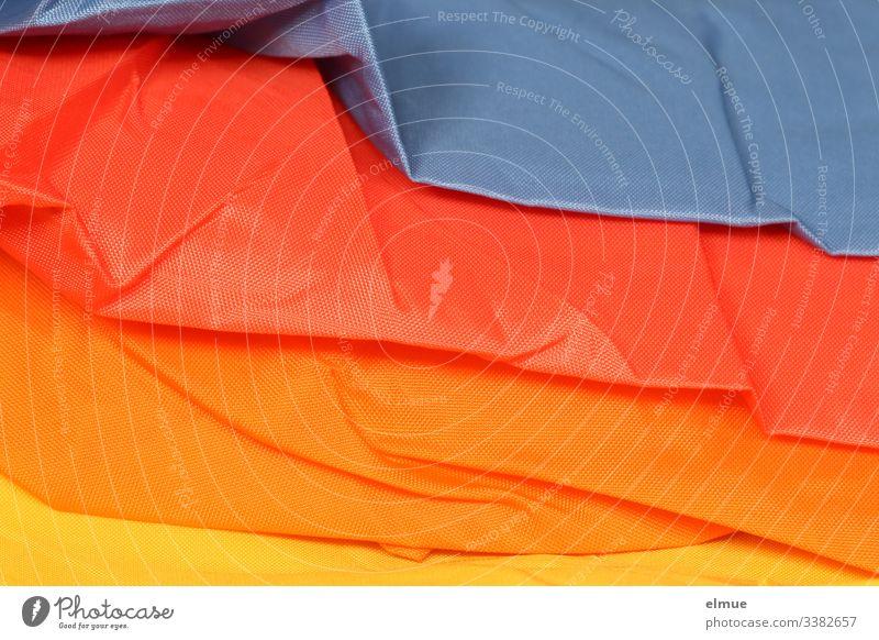 bunter Regenschirm ungeöffnet Stoff Farbe Regenbogenfarben blau rot orange gelb Lagen Regenschirmstoff geschlossen verschiedenfarbig Falte wasserdicht praktisch