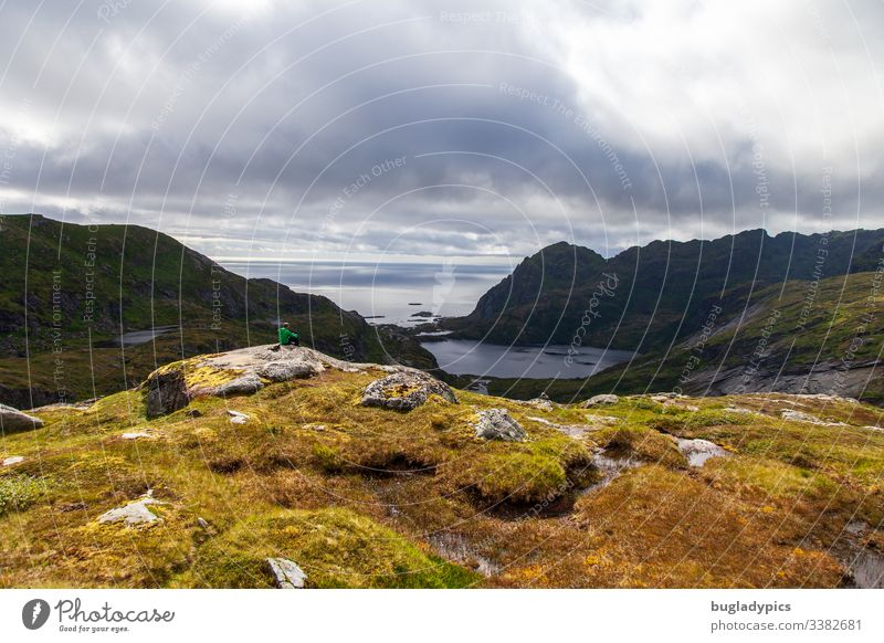 Eine Person sitzt auf einem Felsen und genießt den Blick von den Bergen auf den Lofoten auf das Meer bei einer Wanderung. Lofoten Inseln Norwegen Norwegenurlaub