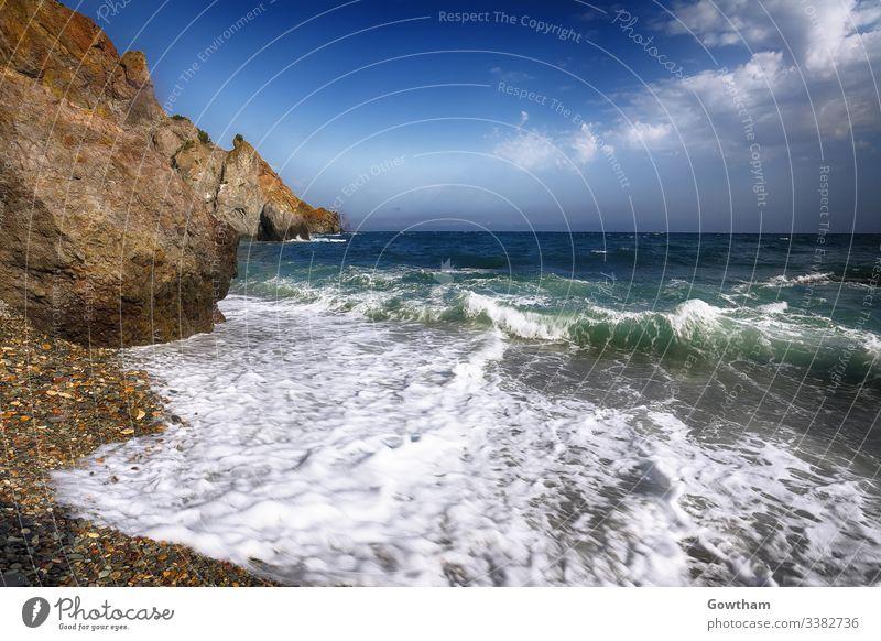 Meereswellen, die an der Küste brechen und über die Kieselsteine am Meeresufer fließen Sonnenaufgang Abenddämmerung winken Strand Farben Schönheit