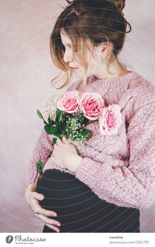 Junge schwangere Frau mit einem Rosenstrauss Schwangerschaft Mama Warten Familie Liebe drittes Trimester Monat Wochen natürlich wirklich offen echte Frau