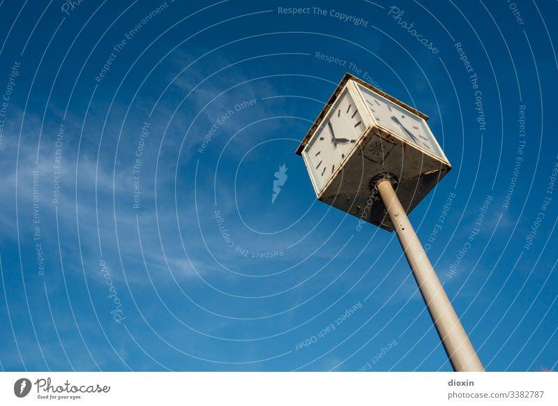 Alte, defekte Stadtuhr, die zwei verschiedene Zeiten vor einem blauen Himmel mit weißen Schleierwolken anzeigt Uhr Uhrenzeiger Zeitpunkt Ziffern & Zahlen