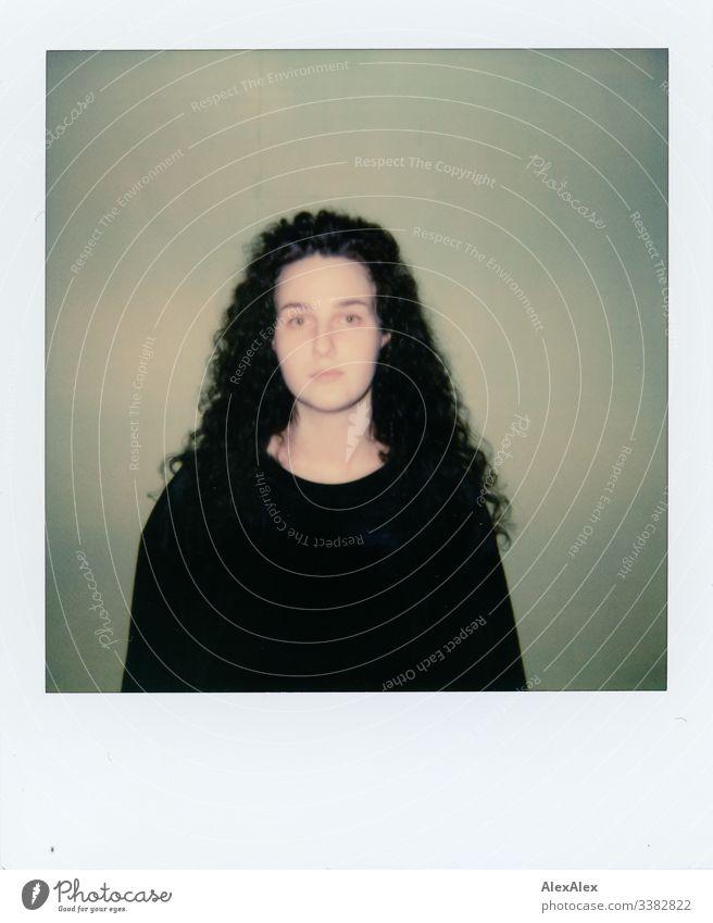 Analoges Polaroid- Portrait einer jungen Frau vor grüner Wand Blick in die Kamera Porträt Zentralperspektive Schwache Tiefenschärfe Kunstlicht Tag