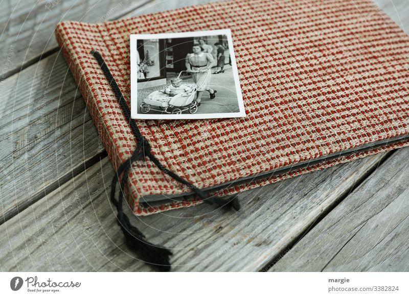 Ein altes Fotoalbum liegt auf einem Holztisch. Ein Foto mit einer Mutter die einen Kinderwagen mit einem Kleinkind schiebt. Fotografie Nostalgie Frau Junge Frau