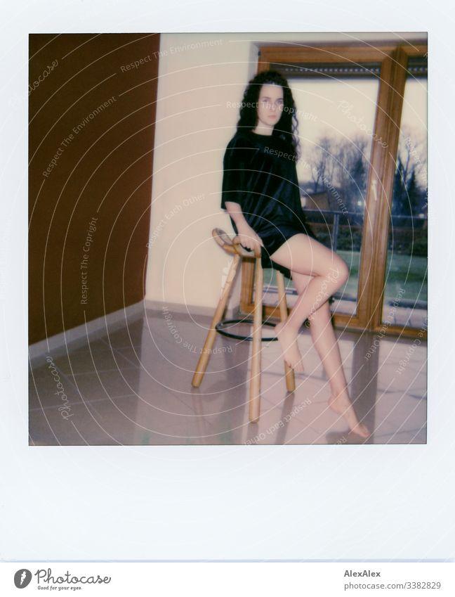 Analoges Polaroid- Portrait einer jungen Frau vor Balkonfenster Blick in die Kamera Porträt Zentralperspektive Schwache Tiefenschärfe Kunstlicht Tag