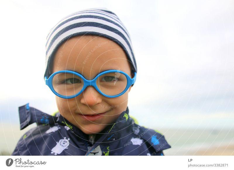 hübsches Kind mit Brille, das in die Kamera schaut Achtsamkeit Kinderspiel Kindheitserinnerung Kinderwunsch Kindheitstraum Inokenz Glück, Emotionen Gefühl