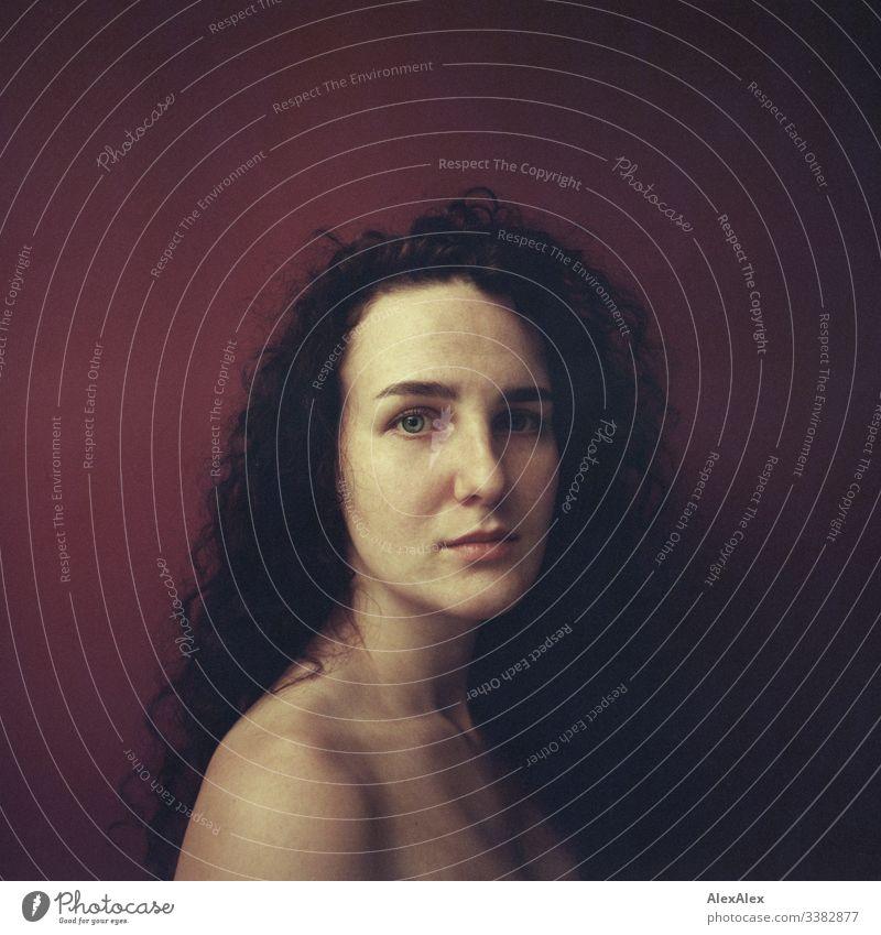 Analoges Portrait einer jungen Frau vor roter Wand Blick in die Kamera Porträt Zentralperspektive Schwache Tiefenschärfe Kunstlicht Tag Textfreiraum rechts