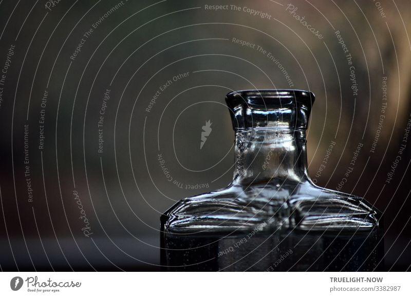 """Hals einer viereckigen Glasflasche, die das Tageslicht bündelt und reflektiert. Vor unscharfem  Hintergrund Reflexion & Spiegelung,"""" Nahaufnahme"""