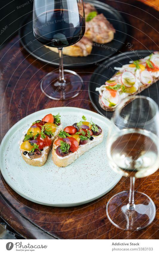 Sandwiches mit Kirschtomaten auf Brot auf Tisch mit Wein Tomaten Kirsche Belegtes Brot Zuprosten Glas lecker Lebensmittel geschmackvoll Feinschmecker Getränk
