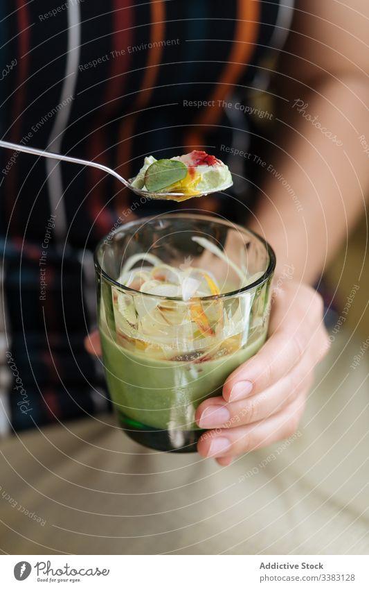 Person, die im Café ein buntes Dessert aus Glas isst Götterspeise farbenfroh geschmackvoll lecker frisch süß Lebensmittel Schalen & Schüsseln grün Frucht kalt