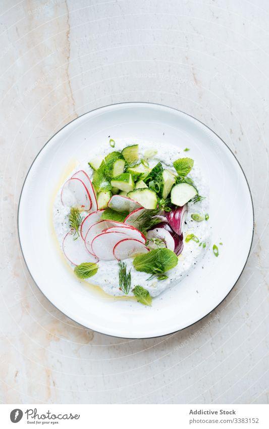 Radieschensalat mit Zucchini, roten Zwiebeln und saurer Sahne im Teller Rettich Salatbeilage Kraut Lebensmittel frisch lecker geschmackvoll Gemüse Speise