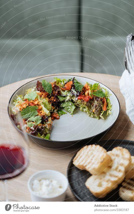 Salat der gehobenen Küche mit Meeresfrüchten und Brot im Restaurant Salatbeilage Haute Cuisine Teller Speise Octopus Tomaten gebraten Scheibe Spielfigur