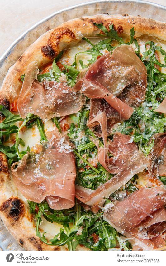 Köstliche Pizza mit Fleisch im Restaurant Speck Kraut Grün Teigwaren gebacken Italienisch Lebensmittel Mahlzeit Küche geschmackvoll Mittagessen frisch Tisch